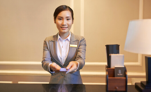 Smiling receptionist giving electronic key to guest