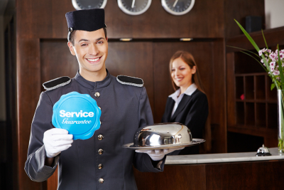 bell boy smiling with smiling receptionist at the back